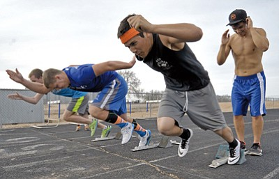 Matt Hinshaw/The Daily Courier<br>Jared Chavez, Michael Brillhart and Travis Rowitsch practice their starts out of the blocks while David Lemcke, right, holds the blocks for Chavez during team practice Feb. 20 in Chino Valley.