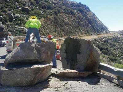 ADOT/Courtesy photo<br>A Department of Transportation crew works to break up a 20-ton boulder Wednesday that rolled onto Highway 89 south of Yarnell March 2. ADOT officials said heavy rains from a powerful storm dislodged it from the mountainside above.