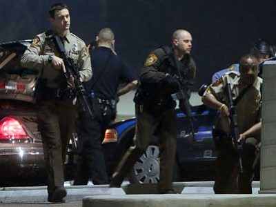 St. Louis Post-Dispatch, Laurie Skrivan/The AP<br> Police mobilize in the parking lot of the Ferguson Police Station after two police officers were shot while standing guard in front of the Ferguson Police Station in the early morning hours Thursday, March 12.