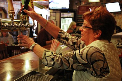 Max Efrein/The Daily Courier<br /><br /><!-- 1upcrlf2 -->Roxane Nielsen pours a draft beer from the pub's new beer-taps.
