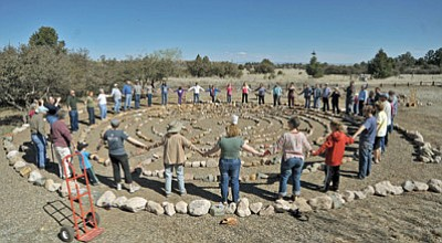 Matt Hinshaw/The Daily Courier. Community members hold hands when they finish the project.