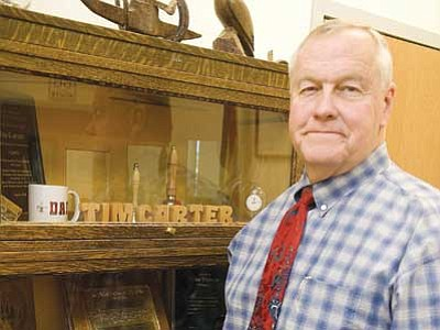 Les Stukenberg/The Daily Courier<br> Yavapai County Schools Superintendent Tim Carter poses in his office with some of the mementoes from his long tenure in education.