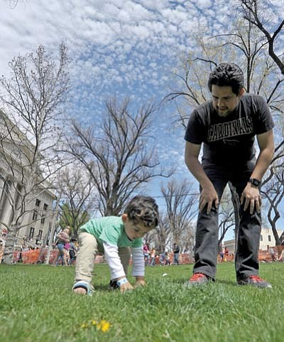 Matt Hinshaw/The Daily Courier<br /><br /><!-- 1upcrlf2 -->Atticus Nieto, 1 1/2, picks up an Easter egg while his dad Alberto looks on during The Great Prescott Easter Egg Hunt Saturday morning at the Courthouse Plaza in downtown Prescott.