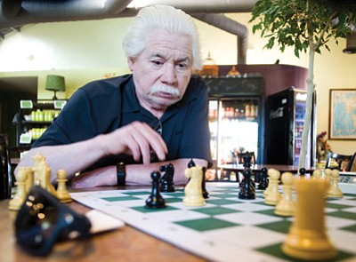 Les Stukenberg/The Daily Courier<br /><br /><!-- 1upcrlf2 -->Prescott College alumnus Tony Ebarb considers a move in a chess game at the Wild Iris Coffee Shop in Prescott.