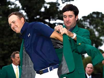 Darron Cummings/The Associated Press<br> Bubba Watson helps Jordan Spieth put on his green jacket for the second time after winning the Masters golf tournament Sunday in Augusta, Ga.