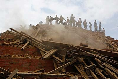 Volunteers help remove debris of a building that collapsed at Durbar Square, after an earthquake in Kathmandu, Nepal, Saturday, April 25, 2015. A strong magnitude-7.9 earthquake shook Nepal's capital and the densely populated Kathmandu Valley before noon Saturday, causing extensive damage with toppled walls and collapsed buildings, officials said. (AP Photo/ Niranjan Shrestha)