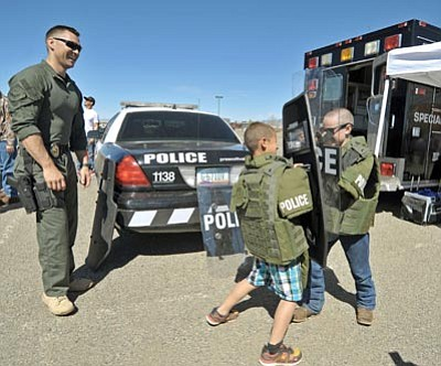 Prescott Valley Police and S.W.A.T. officer Scott Rudolph laughs as Jeremiah Smith, 8, left, and Tanner Carlise, 9, slam into each other trying out the department's riot gear during the fifth annual Salute to Heroes event at the Prescott Valley Event Center on March 21. (Matt Hinshaw, file/The Daily Courier)