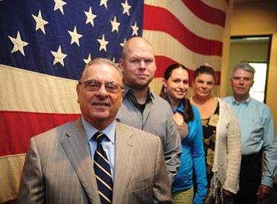 Dr. Cameron K McKinley Vet Center team leader Tony Stanisci, from left, and staff members Justin Krieger, Rachel Evans, Catherine Brennon and Chuck Cean stand in front of a U.S. Flag flown over Khe Sahn United States Marine Corps base in Vietnam in 1968. (Les Stukenberg/The Daily Courier)