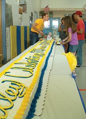 Peter Dorsey, who teaches the English language learners classes at Miller Valley Elementary School, cuts and serves pieces from a 99-foot-long cake at the school's 99th anniversary celebration Friday night, May 1. (Les Bowen/The Daily Courier)