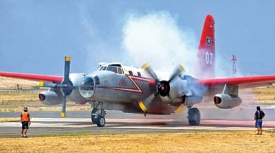 Matt Hinshaw/The Daily Courier, file<br>Smoke pours out of an engine of a fire tanker after being refuled and reloaded with fire retardent at the Prescott Fire Center in 2013 before heading to battle the Yarnell Fire.