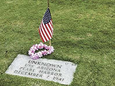 The gravesite, in Punchbowl National Cemetery in Honolulu, Hawaii, of an unknown person who died aboard the USS Arizona during the attack on Pearl Harbor is adorned with a flag. (Courtesy photo)