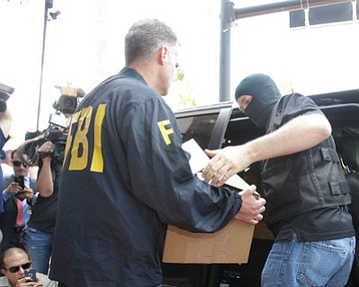 "Wilfredo Lee/The Associated Press<br>Federal agents load a van with boxes of evidence taken from the headquarters of the Confederation of North, Central America and Caribbean Association Football (CONCACAF,) Wednesday, May 27, 2015, in Miami Beach, Fla. Swiss prosecutors opened criminal proceedings into FIFA's awarding of the 2018 and 2022 World Cups, only hours after seven soccer officials were arrested Wednesday pending extradition to the U.S. in a separate probe of ""rampant, systemic, and deep-rooted"" corruption."