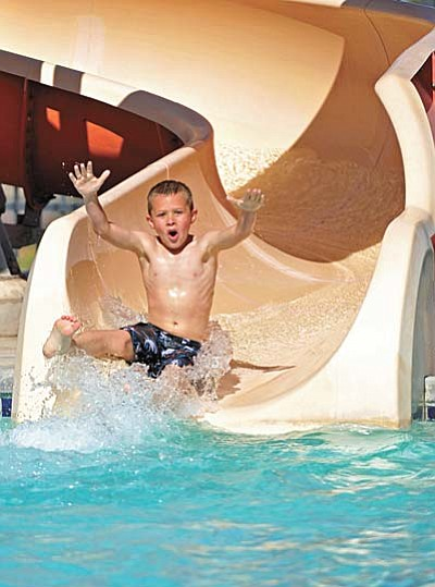 Matt Hinshaw/The Daily Courier<br /><br /><!-- 1upcrlf2 -->Bryce Parker, 8, cheers as he glides through the water slide at the Chino Valley Aquatic Center Wednesday afternoon in Chino.