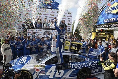 Nick Wass/The Associated Press<br>Jimmie Johnson celebrates in Victory Lane after winning the NASCAR Sprint Cup series race Sunday at Dover International Speedway.
