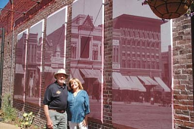 Cindy Barks/The Daily Courier<br>Owners Howard and Nancy Hinson stand in front of the large photo mural that serves at the focal point on the brick wall of the newly-opened Holiday Courtyard on Whiskey Row in downtown Prescott. The Sharlot Hall Museum photo is a historic shot of Whiskey Row, circa 1905. The new outdoor venue is being managed by the Grand Highland Hotel, which is located next door.