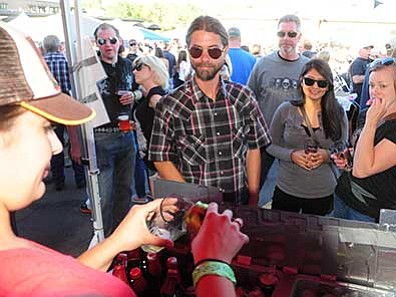 Les Stukenberg/The Daily Courier<br>  SKA Brewing's Abby Patton pours beer for David Drever, Valerie Schweda and Carly Weideman during the Party in the Pines at the Park Plaza Shopping Center in Prescott Saturday night.