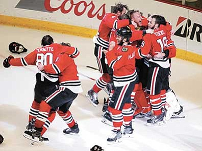 Charles Rex Arbogast/The AP<br> Members of the Chicago Blackhawks celebrate after defeating the Tampa Bay Lightning in Game 6 of the NHL hockey Stanley Cup Final series on Monday, June 15, in Chicago. The Blackhawks defeated the Lightning 2-0 to win the series 4-2.