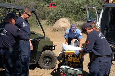 Scott Orr/Daily Courier<br>A man who fell on Trail 62 in the Prescott National Forest is checked by paramedics before being taken to a hospital Wednesday, June 17.