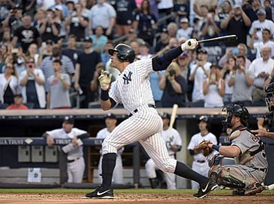 Bill Kostroun/The Associated Press<br>Alex Rodriguez follows through on a home run during the first inning against the Tigers on Friday at Yankee Stadium in New York. The home run was his 3,000th career hit.