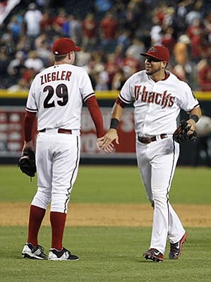 Ross D. Franklin/The Associated Press<br>Brad Ziegler (29) and David Peralta celebrate a win against the Padres after the final out Friday night in Phoenix.