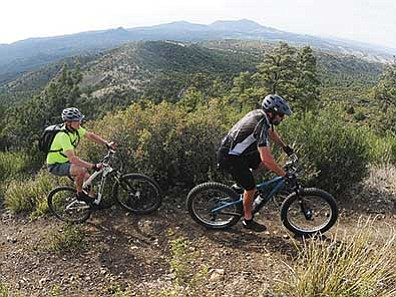 Les Stukenberg/The Daily Courier<br> Ryan Winkelman and Dave Sewell ride the Ranch Trail with Goldwater Lake in the background from Senator Highway on May 13.