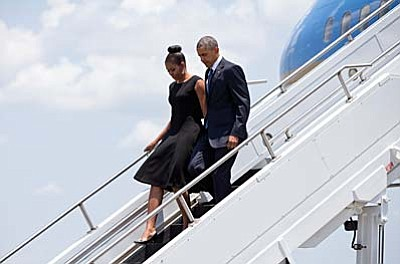 President Barack Obama and first lady Michelle Obama arrive on Air Force One, Friday, June 26, 2015, at Joint Base Charleston near Charleston, S.C., en route to services honoring the life of Reverend Clementa Pinckney at the College of Charleston TD Arena in Charleston, S.C. Pinckney was one of the nine people killed in the shooting at Emanuel AME Church last week in Charleston. (AP Photo/Carolyn Kaster)