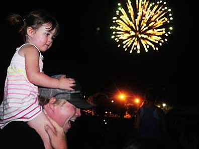 Alan and Quinn Sprang enjoy the fireworks show during the 2014 Fourth of July celebration at Pioneer Park in Prescott.