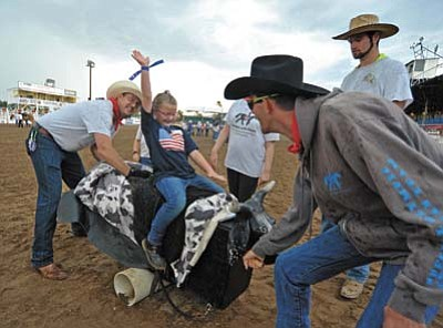 "Matt Hinshaw/The Daily Courier<br>Joeli Knott, 7, rides a bull while Horses With Heart volunteers Jeremy Owns, right, and Josh Lindeblom rock the bull back and fourth and fellow volunteer Koty Dudman, back right, looks on Monday evening during the Happy Hearts Rodeo for Exceptional Children, before the first performance of the Prescott Frontier Days, the ""World's Oldest Rodeo"" at the Prescott Rodeo Grounds."
