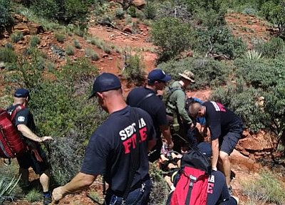 Courtesy photo<br> Sedona firefighters carry a woman who fell about 20 feet off a Bell Rock trail on Sunday, July 19.<br /><br /><!-- 1upcrlf2 --><br /><br /><!-- 1upcrlf2 -->
