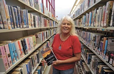 Matt Hinshaw/ The Daily Courier<br> Author and poet Annetter Schober holds up her second published book and first novel Thursday morning at the Chino Valley Library.