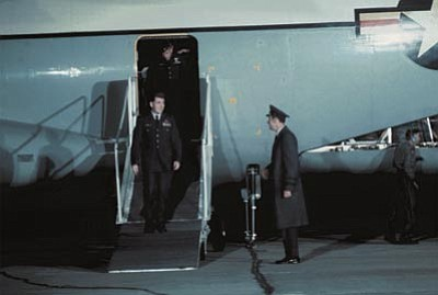 Former POW and U.S. Air Force Col. Ronald E. Byrne Jr., captured Aug. 29, 1965, walks down the ramp of the C-141 Starlifter to be greeted by Gen. Robbins, HQ Military Airlift Command. Byrne was released by the North Vietnamese in Hanoi on Feb. 12, 1973. (Photo from research.archives.gov)