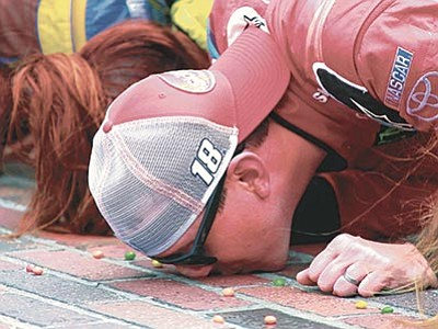 R Brent Smith/The AP<br> Kyle Busch kisses the bricks on the start/finish line after winning the NASCAR Brickyard 400 auto race at Indianapolis Motor Speedway in Indianapolis, Sunday, July 26.