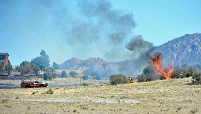 Matt Hinshaw/The Daily Courier<br> Williamson Valley, Central Yavapai, and Chino Valley firefighters work to extinguish a brush fire on Walking Y Lane in Williamson Valley Tuesday afternoon.  The fire started as a permitted burn that got out of control.
