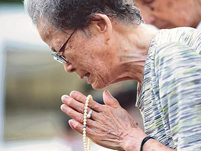 Eugene Hoshiko/The AP<br> A woman cries as she offers prayers at the Peace Park before the 70th anniversary of the Nagasaki atomic bombing in Nagasaki, southern Japan Sunday, Aug. 9.