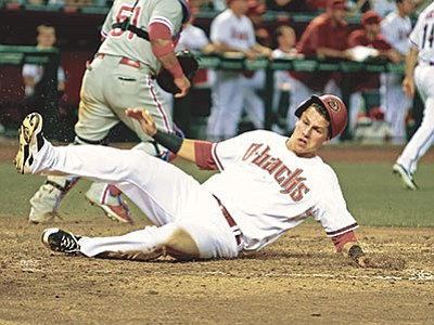 Ralph Freso/The AP<br> Arizona Diamondbacks' Jake Lamb slides across the plate to score against the Philadelphia Phillies on an RBI double by teammate David Peralta during the fifth inning Monday, Aug. 10, in Phoenix.