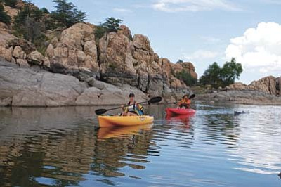 Cindy Barks/The Daily Courier<br>Kayakers Cori Goforth, left, and Louise Berk, right, pass by the water-marked rocks showing noticeably lower levels in Watson Lake on Wednesday, Aug. 12.