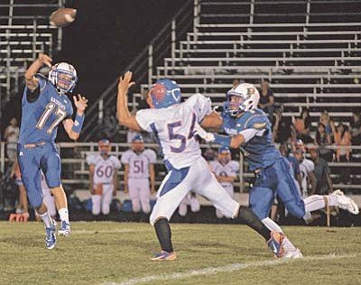 Matt Hinshaw/The Daily Courier<br /><br /><!-- 1upcrlf2 -->Prescott's Ryan Greene (17) passes the ball while Camelback's Joseph Ortega (54) tries to stop him while teammate Marco DiMaria (1) attempts to block him Friday night in Prescott.  The Badgers beat the Spartans 49-7.