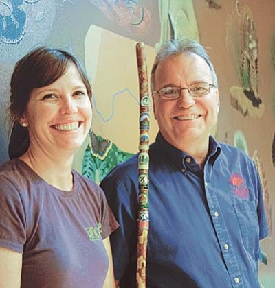 Sue Tone/The Daily Courier<br>Highlands Center Education Director Mara Kack, left, and Executive Director Dave Irvine pose with the Center's hiking stick with Hiking Spree medallions from the past seven years.