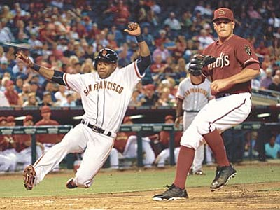 Matt York/The AP<br> San Francisco Giants' Alejandro De Aza scores on a wild pitch as Arizona Diamondbacks pitcher Andrew Chafin waits for the throw during the sixth inning Wednesday, Sept. 9, in Phoenix.