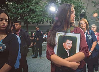 A woman holds a photograph during a ceremony at the World Trade Center site in New York on Friday, Sept. 11, 2015. Sept. 11 victims' relatives marked the anniversary of the terror attacks Friday in a subdued gathering at ground zero, saying their determination to commemorate their loss publicly hadn't dimmed even as 14 years have passed and crowds at the ceremony have thinned. (AP Photo/Bryan R. Smith)
