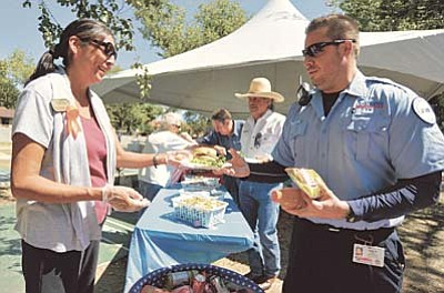 Matt Hinshaw/The Daily Courier<br>Las Fuentes Director of Dining Services Kris Sekaquaptewa hands Lifeline EMT Tyler Arnold a cheeseburger during the Las Fuentes Patriot Day Block Party in honor all emergency responders Friday September 11 in Prescott.