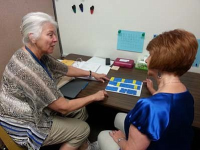 Karen Benson, Reading Specialist at Taylor Hicks Elementary, left, demonstrates the Barton Reading and Spelling System to volunteer Renee Klohr. (Courtesy photo)