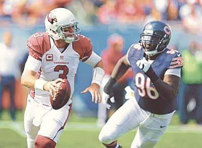 In this Sunday, Sept. 20, 2015 file photo, Arizona Cardinals quarterback Carson Palmer (3) scrambles away from Chicago Bears defensive tackle Jarvis Jenkins (96) during the first half of an NFL football game in Chicago. Palmer threw for four touchdowns to lead the Arizona Cardinals to a 48-23 victory over the Chicago Bears, who lost Jay Cutler to a pulled hamstring Sunday.  (AP Photo/Michael Conroy)