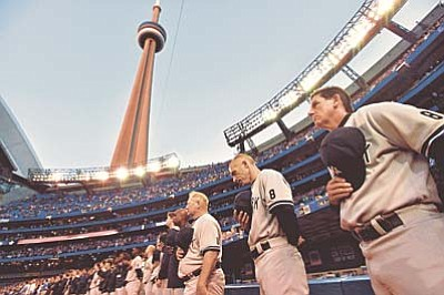 New York Yankees manager Joe Girardi, second from right, and players and coaches take part in a moment of silence as they wear the No. 8 to remember Hall of Fame catcher Yogi Berra, who died Tuesday, before the Yankees' baseball game against the Toronto Blue Jays in Toronto on Wednesday, Sept. 23, 2015. (Nathan Denette/The Canadian Press via AP)