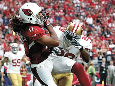 Ross D. Franklin/The AP<br> Cardinals wide receiver Larry Fitzgerald scores a touchdown as San Francisco 49ers strong safety Jaquiski Tartt tries to defend during their NFL football game Sunday, Sept. 27, in Glendale.