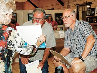 Sue Tone/The Daily Courier<br> Kay Cross, left, holds a photography entry as judges Dennis O'Reilly, middle, and Don Messerschmitt examine and score the print at the Prescott Rodeo Grounds in preparation for the opening of the Yavapai Fair on Thursday, Oct. 1.