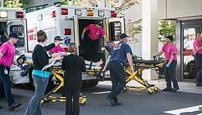 Aaron Yost/Roseburg News-Review via AP<br> A patient is wheeled into the emergency room at Mercy Medical Center in Roseburg, Oregon, following a deadly shooting at Umpqua Community College in Roseburg on Thursday.