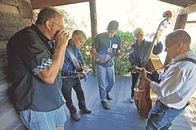 Matt Hinshaw/The aDaily Courier<br /><br /><!-- 1upcrlf2 -->A group of folk musicians gather on the porch of the Governors Mansion and jam Saturday morning during the 37th Annual Folk Music Festival at the Sharlot Hall Museum in downtown Prescott.