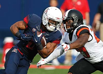 Arizona wide receiver Nate Phillips, left, runs the ball against Oregon State during the second half of an NCAA college football game, Saturday, Oct. 10, 2015, in Tucson, Ariz. (AP Photo/Rick Scuteri)