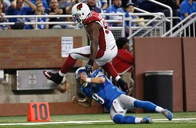 Arizona Cardinals defensive end Cory Redding (90) jumps over Detroit Lions quarterback Matthew Stafford (9) after intercepting a pass during the first half Sunday, Oct. 11, in Detroit. (Duane Burleson/The Associated Press)
